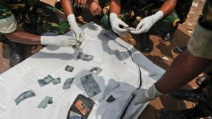 Rescue workers sort out belongings retrieved from bodies found underneath the remains of the Rana Plaza (9 May 2013)