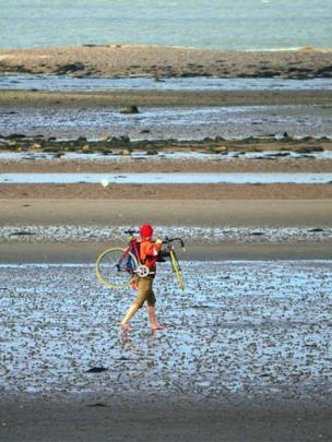 Man carrying a bike on a beach