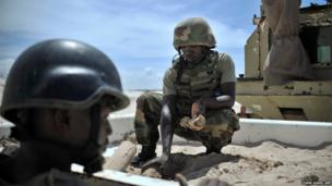 Soldiers unload unexploded ordnance from a trailer at a site near Mogadishu