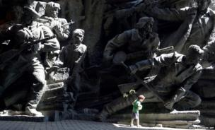 A boy walks in front of a monument at the World War II open-air museum