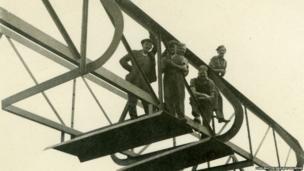 Men standing on a bridge