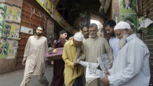 People in Lahore read about the election on Sunday morning