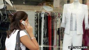 Woman walks past a shop while on the phone