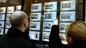Generic couple looking at estate agent window