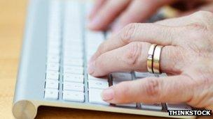 An old lady's hands on a computer keyboard