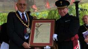 Mayor Doug Williams hands the freedom scroll to Col Tom Bonas