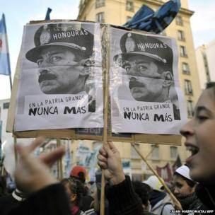 """A demonstrator holds a placard with the portrait of Videla and the inscription """"Honduras-Never Again In The Big Motherland"""" during a protest against the coup d'etat in Buenos Aires, on July 2, 2009."""