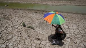 A schoolgirl carries an umbrella to protect herself from the heat as she walks past a dried pond on the outskirts of Jammu