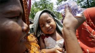 An Indian woman, participating in a rally to protest increasing violence against women and girls, sprinkles water on her daughter's face to beat the heat in Bhubaneswar