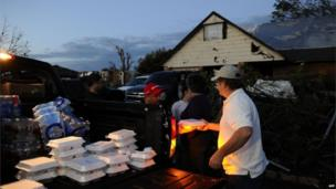 Derick Brock from Mercy Chefs distributes hot food to tornado victims at their devastated neighbourhood 21 May, 2013 in Moore, Oklahoma.