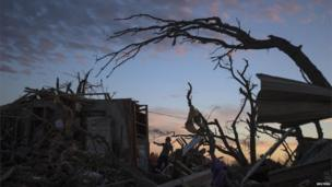 A woman searches for possessions at sunset after the suburb of Moore, Oklahoma was left devastated by a tornado, 21 May 2013