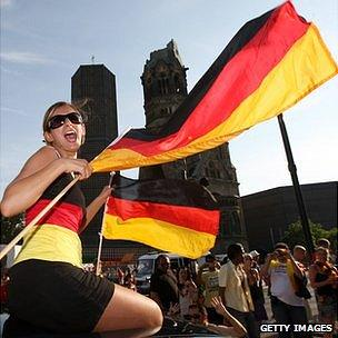 A German football supporter waves national flags on top of a car on the Kurfuerstendamm, Berlin.