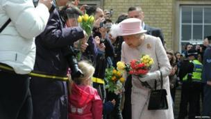 The Queen accepts flowers from children outside Cambridge railway station