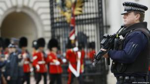 An armed police officer stands guard as British soldiers march through a gate