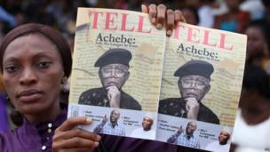 A woman sells magazines with a portrait of Chinua Achebe in Awka, 22 May