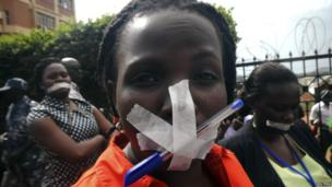Employees of Uganda's Daily Monitor newspaper, with their mouths taped shut, protest in the capital, Kampala (20 May 2013)