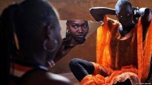 Bineta Ndiaye looks at herself in the mirror as her friend Coumba Faye fixes her hair in the village of Ndande in Senegal