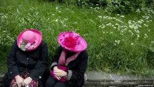 Two ladies have a conversation while sitting on a wall at the Chelsea Flower Show in London