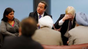Prime Minister David Cameron, (centre) and Mayor of London Boris Johnson (right) speak to members of the local community, during a visit to Woolwich,