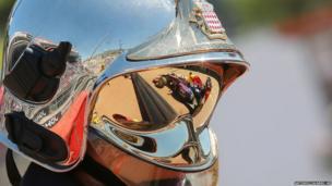 Red Bull driver Sebastian Vettel's car is reflected on a fire fighter's helmet