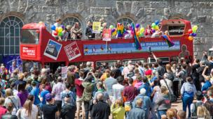 People on an open-top bus taking part in the parade