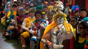 Dozens of clowns sit together, one of them wearing an armour and golden headgear.