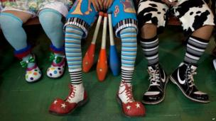 A row of colourful shoes of three clowns