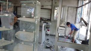 Iraqis clear up damaged shop, 28 May.