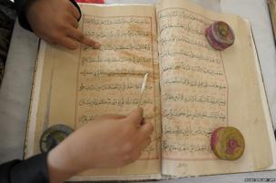 An Indian paper conservator restores an antique copy of the Koran at Chowmahalla Palace in Hyderabad