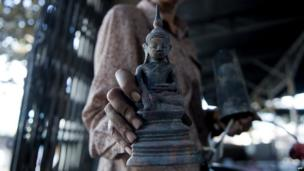A woman holds a statue of a Buddha inside a demolished shop in Lashio, Burma