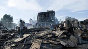 A camera man films the wreckage following a fire which broke out during the violence in Lashio