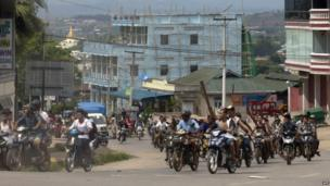 Hundreds of Buddhists on motorcycles armed with sticks patrol in the streets of in Lashio, northern Shan State, Myanmar, Wednesday, May 29, 2013.