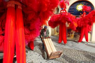 A worker pushes a cart past French actors of the International Show Parade theatre company relaxing in Bucharest