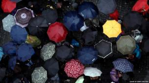 People carry umbrellas as they walk across the Old Town Square during a rainstorm in Prague