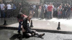 In Istanbul a protester reacts as riot police use water cannon to disperse the crowd