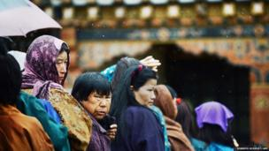 Bhutanese voters wait to cast their vote as they line up outside a polling station in Paro
