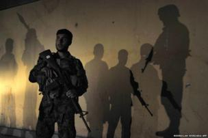 An Afghan security official is surrounded by the shadows of colleagues as he keeps watch at the scene of an attack in Jalalabad