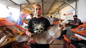 A Benghazi fishmonger holds a fish, Libya - Thursday 30 May 2013