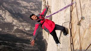 Man poses on Chang Kong Cliff Road in Shaanxi province, China