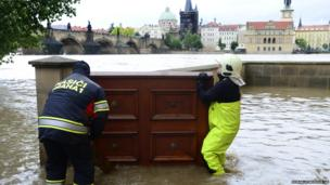 Fireman carry furniture to create a flood barrier in central Prague (2 June 2013)