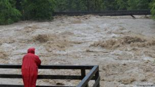 A local resident watches the swollen river Saalach, in Lofer in the Austrian province of Salzburg, Sunday, June. 2, 2013