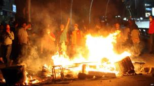 Protesters stand in front of makeshift fires in Ankara early on 3 June 2013.