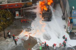 Firefighters attempt to extinguish a burning petrol tanker at a military-run petrol station in Hanoi, Vietnam