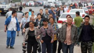 Relatives of victims leave the scene of a blaze from Baoyuan poultry plant at Dehui, in north-east China's Jilin province, 3 June 2013