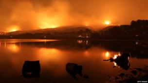 Fires burn on the hills around a lake near Los Angeles, California 2 June 2013