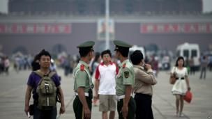 Chinese paramilitary policemen monitor visitors as they stand guard in Tiananmen Square on the 24th anniversary of the deadly 1989 crackdown on pro-democracy protestors in Beijing 4 June 2013