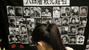 A woman reads a book in front of portraits of victims of the crackdown of the 4 June 1989 pro-democracy movement in Beijing's Tiananmen Square at the June 4 Memorial Museum run by pro-democracy activists at City University in Hong Kong, 3 June 2013 to commemorate the 24th anniversary of the crackdown