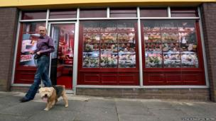 Kevin Maguire walks his dog past a vacant shop in Belcoo, Northern Ireland