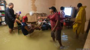 People try to watch television inside their flooded home in Mexico's resort city Cancun