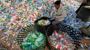 A worker separates plastic bottles at a recycling depot in Beijing